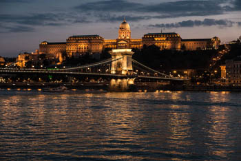 view of the illuminated Royal Palace in Buda and the Chain bridge at dusk