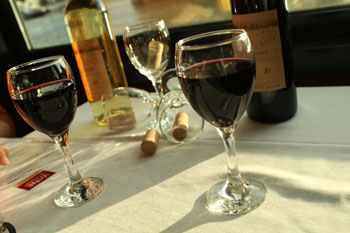 3 glasses of wine, 2 red 1 white on a white-clothed table onboard a cruise ship