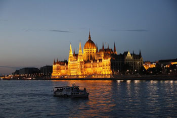 a sightseeing boat plying the danube at the Parliamnet at dusk