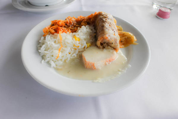 a portion of stuffed cabbage with white rice on a round plate