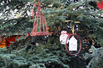 part of a Christmas tree with simple, handmade ornaments hanging from the branches.