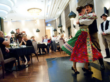a pair in folk costume (the woman in red, green and white) dancing next to the diners