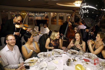 people partying on the New Years Eve cruise ship, gxpsy orchestra playing music