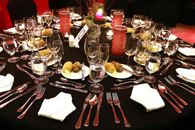 a round table elegantly set with black cloth, silverware and candels on the Europa ship