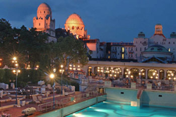 the outdoor pool and the dome sof the gellért bath and hotel at sunset