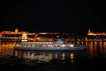 an illuminated white cruise boat on the Danube at night