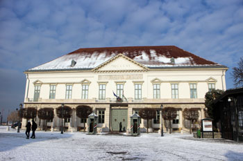 the front facade of the Sandor Palace, the ground covered in snow