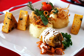 stuffed cabbage with polenta pyramid on a square white plate