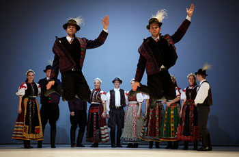 2 folk costumed men jumping in the air with 4 pairs of dancers in the background
