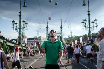 a young man in green T-shirt juggling balls on the bridge