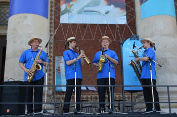 a jazz quartet dressed in blue shirt and wearing a straw hat playing