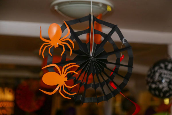 orange and black spiders hanging from the ceiling of the boat