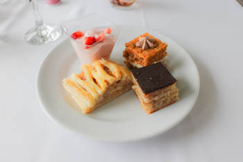 strawberry mousse in shotglass, a piece of strudel, and two other mini cakes on a round white plate