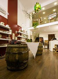 2 wooden barrels, shelves with ceramics bottle sof wine on shelves in the shop