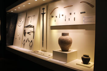 urns, weapoms, jewelry from the ancient times of the city displayed in glass cabinets
