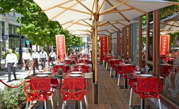the terrace with red chairs and large beige sun umbrellas