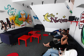small red chairs, and funny paintings on the wall of the hostel's common room