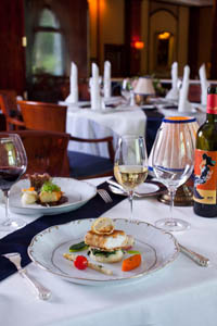 an elegantly set table with a dish on white porcelain plate, a glass of white wine next to it