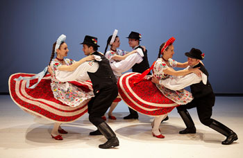 3 couples in folk costume performing a Hungarianfolk dance