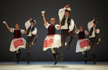 3 folk dance couples jumping on the stage