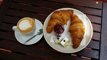 2 croissants, butter and jam and a cappucino