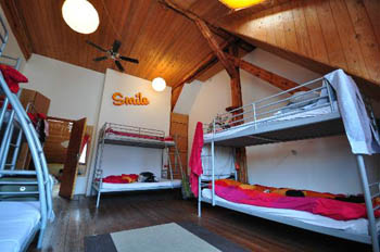 room with bunk beds and red blankets on them, wood paneled ceiling