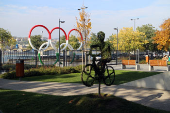 the Olympic five rings and statue of a biker