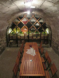 a long cherry stained wooden bench with chairs inside a vaulted stone cellar