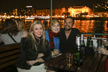 2 ladies and a man sitting on the open deck of a party boat