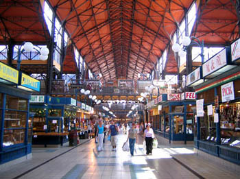 shoppers and tourists walking on the ground level of the market, under an iron structure roof