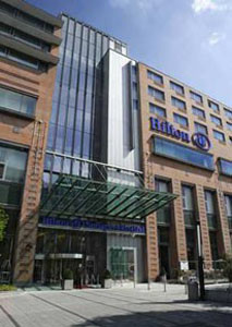 entrance and facade of the hotel with Hilton written in blue