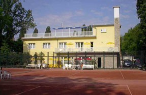 the facade of Hotel Margitsziget with a clay tennis court in front of the building