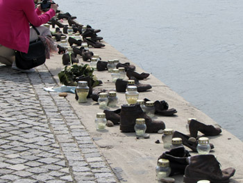 cast iron pairs of shoes with candles next to them on the bank of the Danube