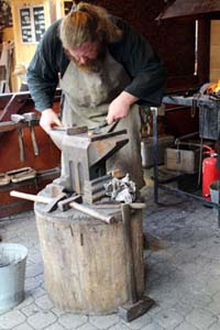 a bearded smith working in a smithy on Vörösmarty sqr.