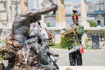 a trumpeter in hussar costume at a bronze statue and fountain
