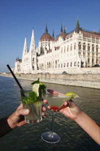 toasting with two glassess of cocktails, on the danube, the Parliament in the background