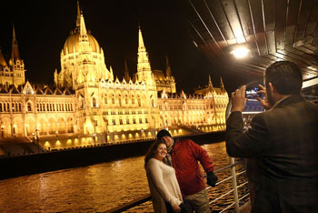 a middle-aged couple is being photograhhed standing on the deck of a ship, the illuminated Parliament in the background