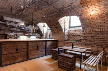 the raw brick covered vaulted interior with a woo table with benches and footstool around it