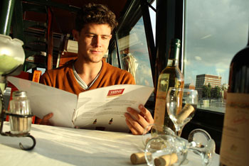 a young man reading sitting at a table anda wine list in a bar