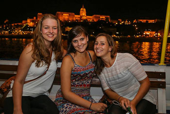 3 young ladies on a tour boat's deck, the illuminated Royla Palace in the background