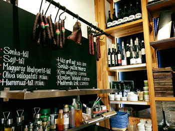 the bar area with a balck board and sausages hanging, wine bottles on shelves