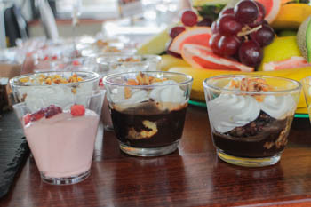 1 strawberry and 2 choco mousse with whipped cream in shot glass, fruits in the background