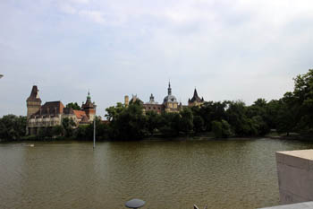 the lake with the towers of Vajdahunyad castle in the background on a cloudy morning