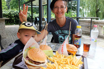 our 5 yr old boy and me eating burgers and fries at a terraced cafe