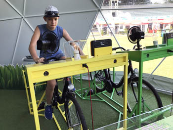 our 13 years old boy on a bike in the inventors' tent