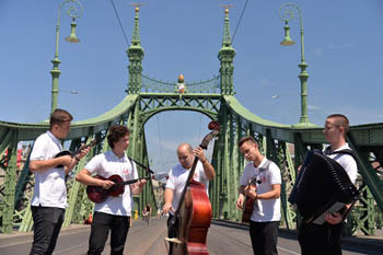 an orchestra dressed in white t-shirt and black trousers playing on the green Liberty bridge