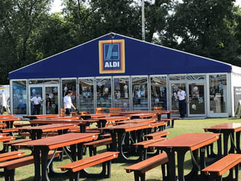 brown wooden tables and benches with an Aldi shop in the background