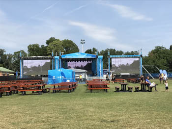 cherry brown benches and giant projectors on a grassy area