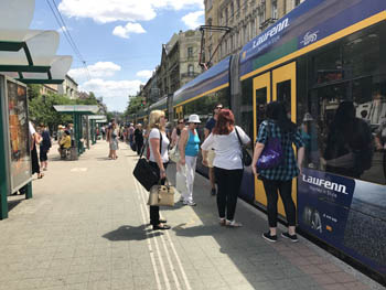people getting on and off the yellow tram 6