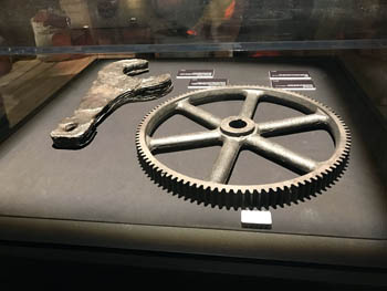 a large metal cog wheel and a wrench in a display cabinet